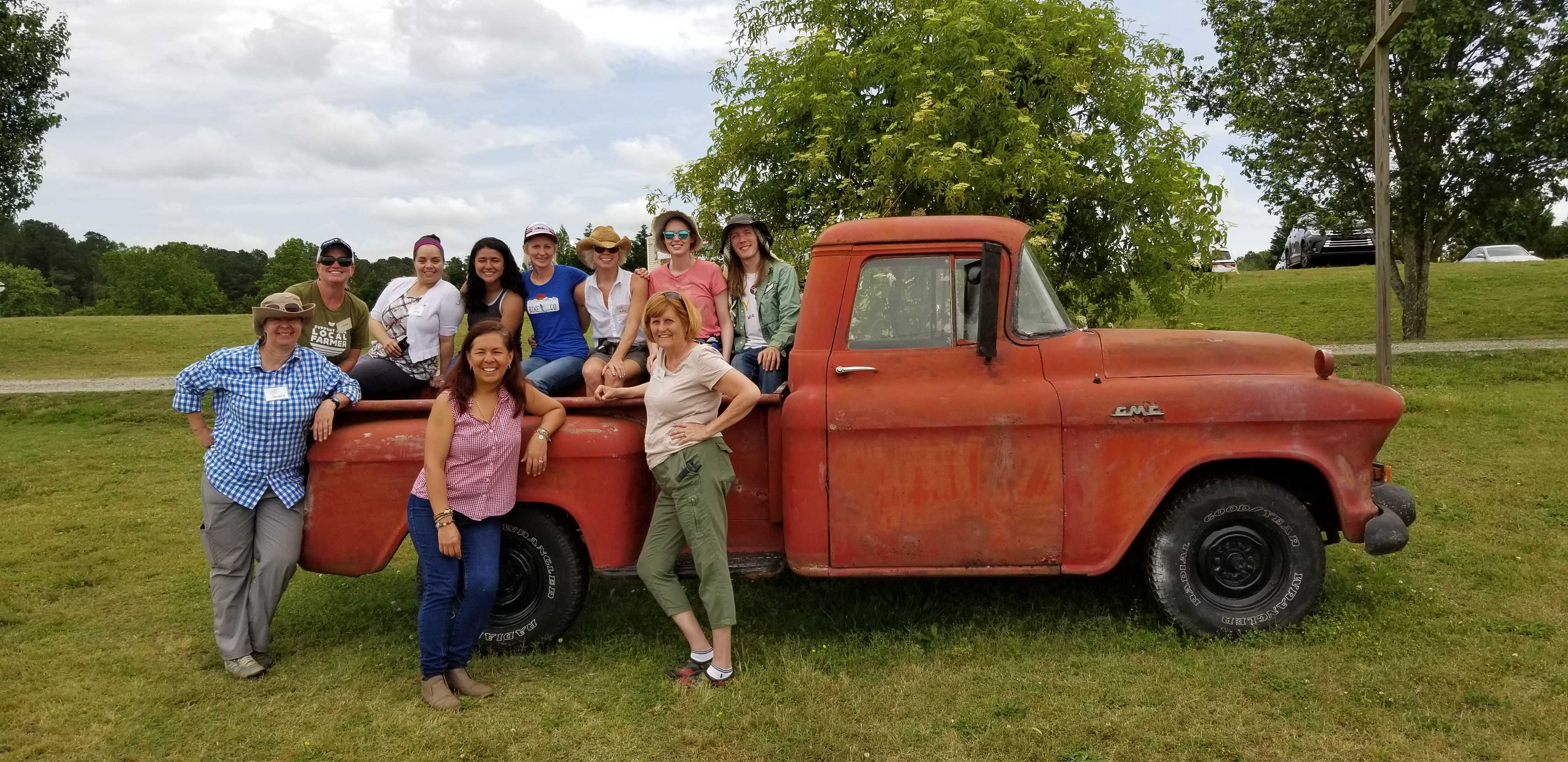 alegre farm field trip staff posing by antique truck